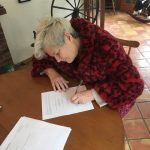 Jude with styled white hair leaning over a round wooden table signing papers with a smile
